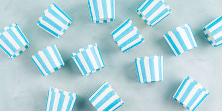 Pastel blue striped paper cases for baking cup cakes on gray background. Sweet pastry concept, flat lay