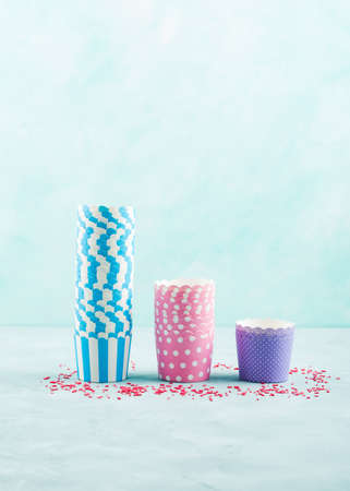Colorful pastel color paper cases for baking cup cakes on gray background. Sweet pastry, birthday party concept