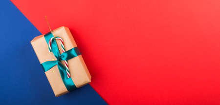 Red and classic blue christmas background with gift box with green ribbon and candy cane. Flat lay Banco de Imagens