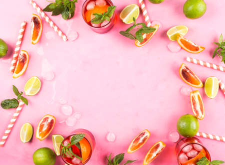 Pink background with ingredients for summer iced red cocktail with blood orange and lime. Frame, copy space