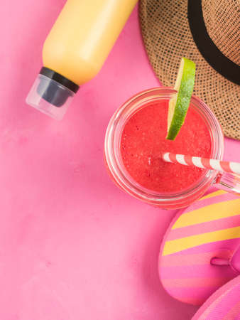 Straw hat, pair of colorful flip flops, yellow sun protection spray and refreshing red watermelon smoothie on pink background. Summer beach vacation relax, vertical