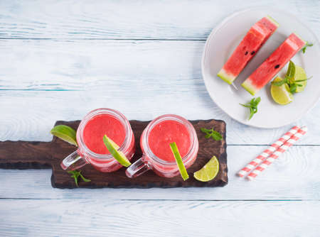 Watermelon smoothie with lime and mint in mason jar on white wooden background. Top view, copy space 스톡 콘텐츠