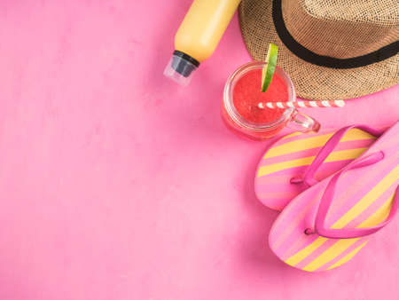 Straw hat, pair of colorful flip flops, yellow sun protection spray and refreshing red watermelon smoothie on pink background. Summer beach vacation relax, copy space 스톡 콘텐츠