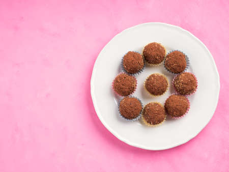 Home made vegan energy protein balls with oats, nuts, almond butter, dates, dried fruit, flax seeds, chocolate nibs on white dish on pink wooden background. Top view, copy space