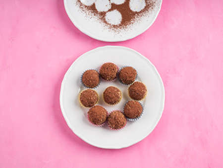 Home made vegan energy protein balls with oats, nuts, almond butter, dates, dried fruit, flax seeds, chocolate nibs on white dish on pink wooden background. Top view