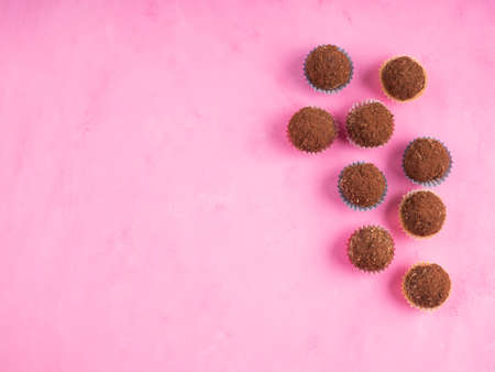 Home made vegan energy protein balls with oats, nuts, almond butter, dates, dried fruit, flax seeds, chocolate nibs in colorful paper cases on pink wooden background. Top view, copy space