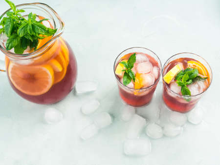 Fresh red cocktail mocktail sangria in pitcher and glasses with ice, mint leaves and lemon and orange slices on bright turquoise background. Top view 스톡 콘텐츠