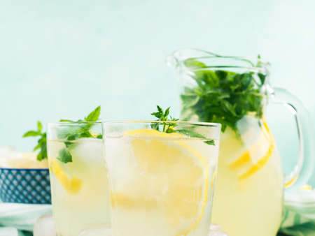Fresh lemonade in jug and glasses with ice, mint leaves and lemon slices on bright gray and blue background. Closeup 스톡 콘텐츠