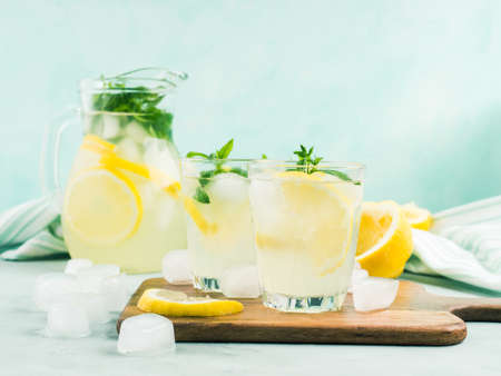 Fresh lemonade in jug and glasses with ice, mint leaves and lemon slices on bright gray and blue background. Closeup Banco de Imagens