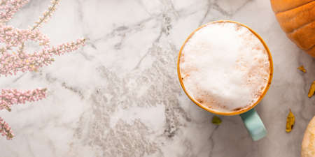 Autumn moody background with mug of latte coffee and pumpkins on marble table. Banner