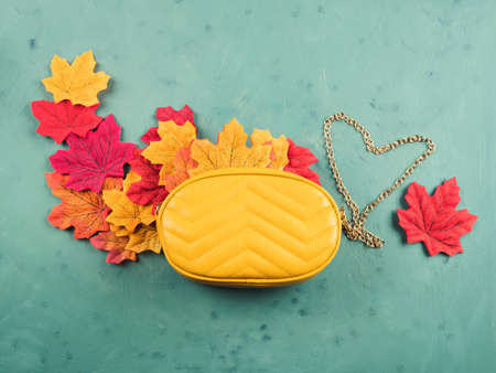 Female trendy yellow mustard handbag with autumn leaves over green background. Flat lay