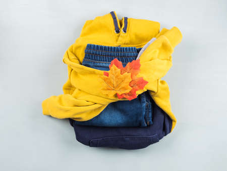 Autumn kids yellow and blue folded outfit with fall maple leaves. Flat lay on pastel blue background. Autumn fashion, wardrobe organization concept Banque d'images