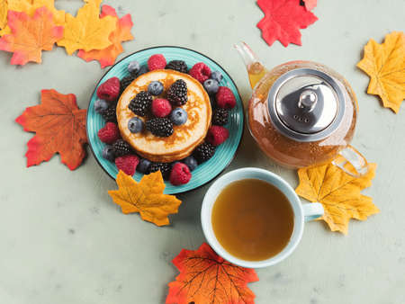 Stack of pancakes with fresh berries served in a dish with green tea with autumn leaves decor 스톡 콘텐츠
