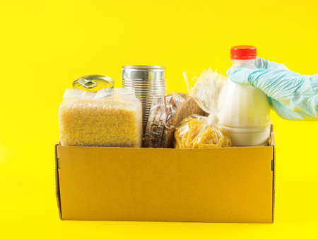 Safe food delivery concept on yellow background with cardboard box full of food staples like milk, canned vegetables, pasta, beans, rise. Blue gloves for Covid prevention