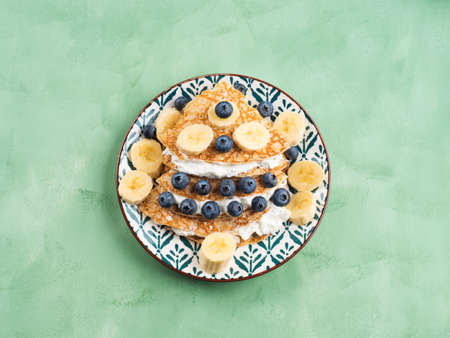 Christmas tree shaped sweet crepes with cream greek yogurt filling and blueberry topping on pastel green table.