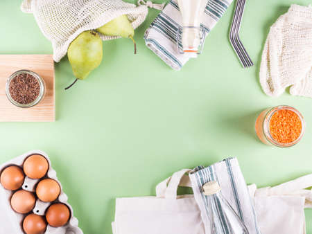 Green zero waste background with reusable accessories for grocery shopping, food storage and lunch