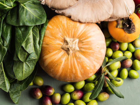 Green background with raw organic vegetable, fruit. Autumn, winter veggies concept, healthy food. Top view Stok Fotoğraf