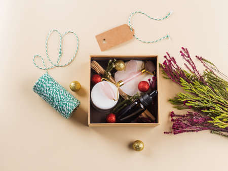 Zero waste beauty christmas new year gift box with flowers. Guasha, essential oil, bamboo toothbrushes, cotton pads, cream.