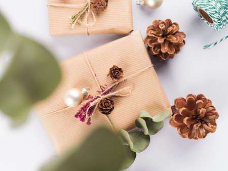Christmas festive scene with wrapped zero waste presents, golden decor, pine cones and eucaliptus on gray background.