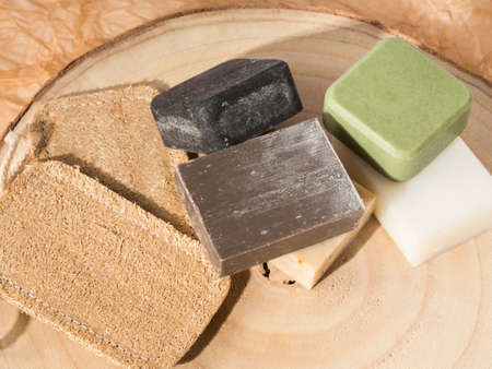 Solid shampoo soap conditioner bar, natural body care eco friendly products and loofah sponges on wooden board and beige neutral paper Stock fotó