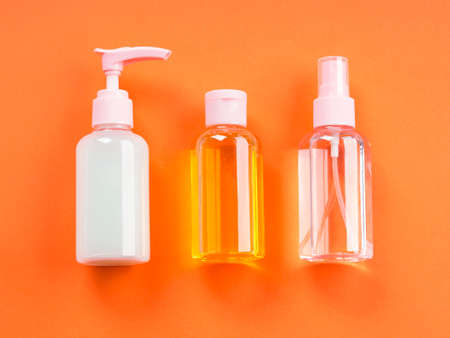 Generic beauty products on orange background. Lotion, tonic, cleanser in bottles
