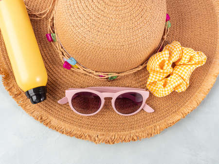 Summer lady straw hat, yellow sun protection spray and sunglasses