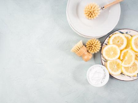 Zero waste plastic free dish house washing brush and natural cleaning product lemon and baking soda. Sustainable lifestyle concept.