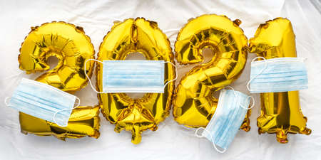 2021 new year numbers golden foil balloons on white sheet with face masks. Saying goodbye to Covid