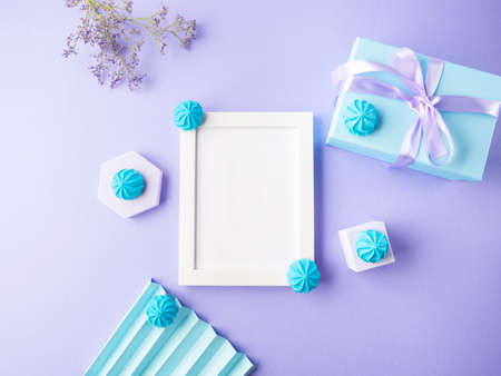 White empty frame on purple background with blue sweet decor, festive flat lay