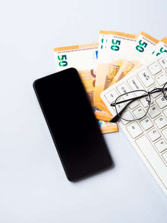 Euro money banknotes, keyboard, smartphone and glasses, online banking, business, student loan concept