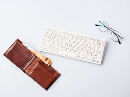 Euro money banknotes in wallet, keyboard and glasses, online banking, business, student loan concept