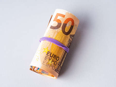 Euro 50 value banknotes roll with rubber on gray background