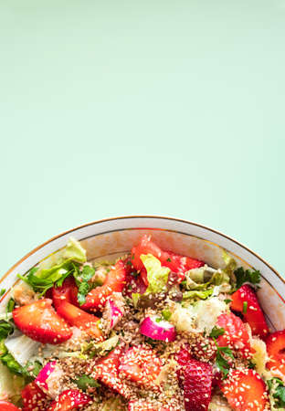 Fresh summer healthy fiber protein vitamin salad in bowl with strawberries, lettuce, tuna, tomatoes