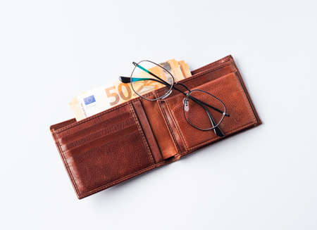 Euro money currency 50 value banknotes in expensive leather wallet and glasses on blue background Stockfoto