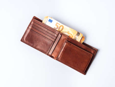 Euro money currency 50 value banknotes in expensive leather wallet on blue background