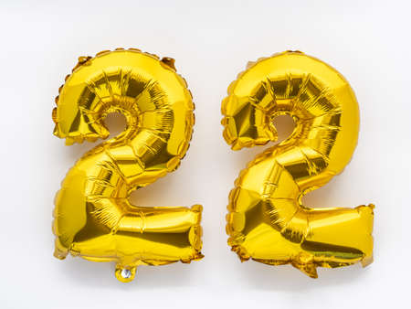 22 golden foil balloon numbers party decor on white background, birthday anniversary concept