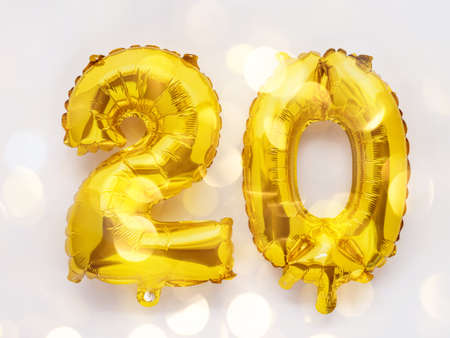 20 golden foil balloon numbers party decor on white background, birthday concept with lights