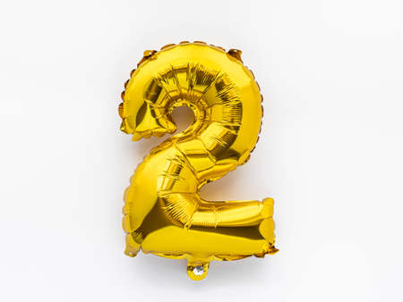 Number 2 golden foil balloon party decor on white background, birthday anniversary concept Stockfoto