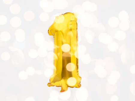 Number 1 golden foil balloon party decor on white background, birthday anniversary concept with festive lights