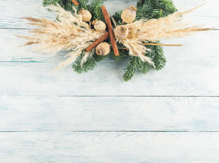 Christmas natural spruce wreath with dry decor, pampas reed and cinnamon on wooden background