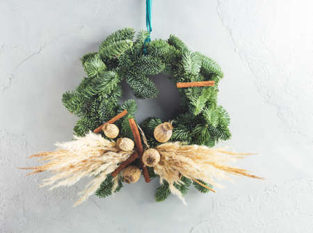 Christmas natural spruce wreath with dry decor, pampas reed and cinnamon over gray wall background