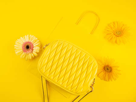 Yellow fashion lady handbag with gerbera flowers on monochrome background with paper shopping bag Stockfoto
