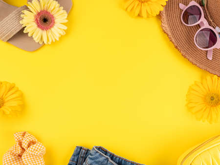 Summer fashion outfit frame background with straw hat, shoes, sunglasses, handbag, flowers on yellow Stockfoto