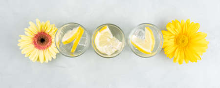 Lemon water drink with ice cubes on stone background with gerbera daisy yellow flowers Stockfoto