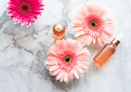 Pink flowers and beauty serum in dropper bottles on marble table. Skin care concept Stockfoto