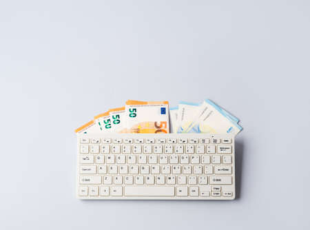 Euro money banknotes under keyboard, online banking, sale of digital info products concept