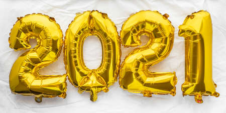 2021 new year numbers in golden foil balloons on white sheet background