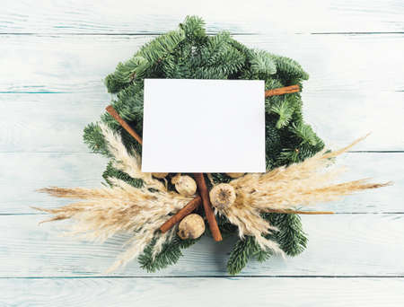 Natural christmas spruce dry decor wreath with white empty greeting card on wooden background Stockfoto