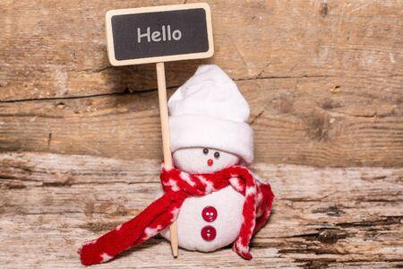 Pequeño muñeco de nieve que muestra una señal con la palabra hola