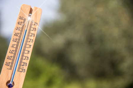 summer heat: thermometer pointing to the sky to symbolize the heat of summer